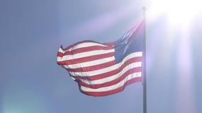 与太阳的美国国旗发出光线后照光 图库摄影