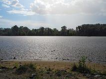 与太阳的阵雨在河 基于由河的一个夏日 免版税库存照片
