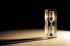 与太阳的阴影和强光的滴漏sandglass在黑暗的背景的 老减速火箭的样式葡萄酒照片 免版税库存照片