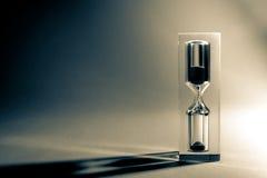 与太阳的阴影和强光的滴漏sandglass在黑暗的背景的 老减速火箭的样式葡萄酒照片 库存照片