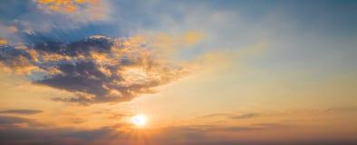 与太阳秋天的日落场面和光芒在背景,温暖的五颜六色的天空中点燃,云彩 库存照片
