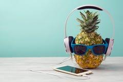 与太阳镜、耳机和巧妙的电话的菠萝在薄荷的背景的木桌上 夏天热带假期 免版税库存图片