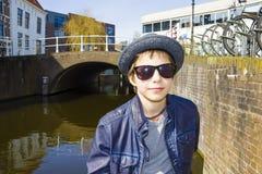 与太阳镜和帽子的逗人喜爱的孩子在一个城市环境里 免版税库存照片