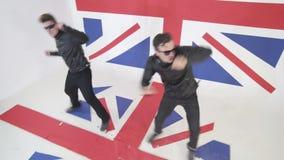 与太阳镜和皮革摩托车夹克的精力充沛的滑稽的男性跳舞 影视素材