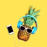 与太阳镜和耳机的时尚菠萝听在智能手机的音乐在黄色背景 免版税库存图片
