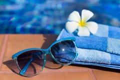 与太阳镜和花的蓬松毛巾在游泳的边界 免版税图库摄影