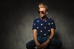 与太阳镜的凉快的时装模特儿坐凳子 免版税图库摄影