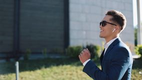 与太阳镜的年轻商人听到在他的智能手机户外和跳舞的音乐的 走在办公室附近的他 影视素材