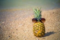 与太阳镜的菠萝在海滩 免版税图库摄影