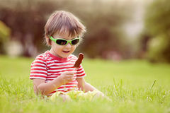 与太阳镜的逗人喜爱的孩子,吃巧克力棒棒糖 图库摄影