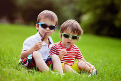 与太阳镜的逗人喜爱的孩子,吃巧克力棒棒糖 免版税图库摄影