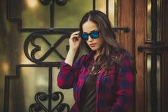 与太阳镜的都市女孩画象在城市 库存照片