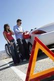 与夫妇倾吐的燃料的警告三角到汽车里 免版税库存照片
