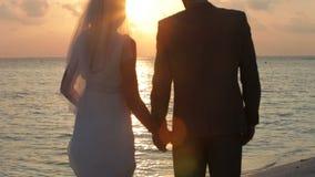 与夫妇的日落在美好的海滩婚礼 免版税库存图片
