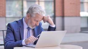 与头疼工作的老商人在膝上型计算机,室外 股票录像