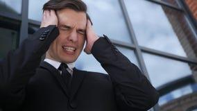 与头疼的沮丧,紧张的年轻商人和问题 库存图片