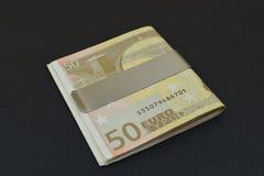 与夹子的欧元在黑桌上 库存图片