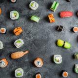 与套的框架在黑暗的背景的日本食物 寿司卷、nigiri、未加工的鲑鱼排和鲕梨 平的位置 顶视图 免版税库存照片