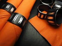 与套餐巾用的小环的橙色餐巾 免版税图库摄影