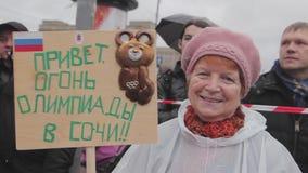 与奥林匹克熊的退休的妇女举行海报 索契奥林匹克圣火接力赛在圣彼得堡 影视素材