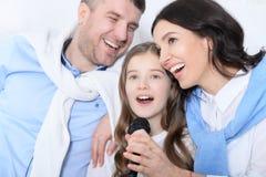 与女儿唱歌卡拉OK演唱的家庭 库存照片