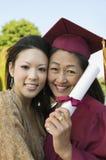 与女儿的女性毕业生举行的程度 图库摄影