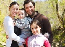 与女儿的愉快的年轻家庭户外 免版税图库摄影