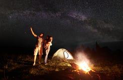 与女儿的旅游家庭有休息在山在晚上在与银河的满天星斗的天空下 免版税图库摄影