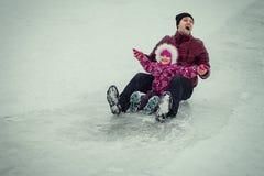与女儿的爸爸辗压雪撬的在冬天公园 免版税库存图片