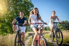 与女儿骑马的快乐的家庭在草甸骑自行车在晴朗 免版税库存照片