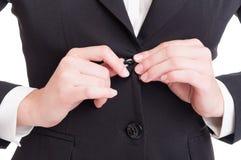 与女商人的特写镜头递闭合值的衣服夹克按钮 免版税图库摄影