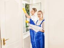 与女孩的专业人清洁窗口在房子里 免版税图库摄影