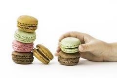 与女孩的甜和五颜六色的法国蛋白杏仁饼干递举行 图库摄影