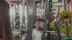 与女孩辅导员的个人训练有大腹部的人的在健身房 与私有教练一起的厚实的肥胖人 股票视频