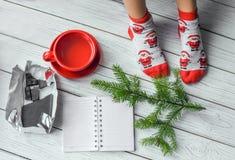 与女孩` s脚的圣诞节照片在明亮的红色袜子、一根冷杉枝杈、一个笔记本和一支铅笔在一个白色木地板上 免版税库存照片