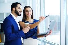 与女性同事或客户的商人在办公室 免版税图库摄影