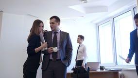 与女性同事调情的人的商人在办公室 股票录像