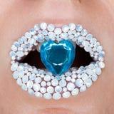 与女性嘴唇的美丽的特写镜头有白色brilliants的和蓝色精采在嘴 构成,在嘴唇的闪烁闪闪发光 免版税库存照片