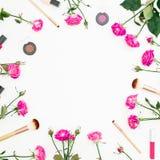 与女性构成的花卉框架与桃红色玫瑰和化妆用品在白色背景 被设色的背景秀丽蓝色概念容器装饰性的深度详细资料域充分的仿效宏观自然超出珍珠浅天空 平的位置,顶视图 免版税库存图片
