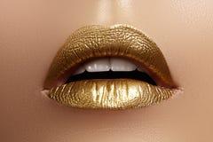 与女性肥满嘴唇的美丽的特写镜头有金子颜色构成的 时尚庆祝构成,闪烁化妆用品 免版税库存图片