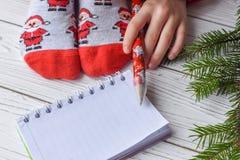 与女性脚的圣诞节照片在明亮的红色袜子、一根冷杉枝杈、一个笔记本和一支铅笔在一个白色木地板上 库存图片