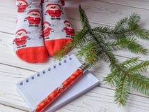 与女性脚的圣诞节照片在明亮的红色袜子、一根冷杉枝杈、一个笔记本和一支铅笔在一个白色木地板上 免版税库存图片