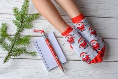与女性脚的圣诞节照片在明亮的红色袜子、一根冷杉枝杈、一个笔记本和一支铅笔在一个白色木地板上 库存照片