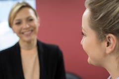 与女性辅导者的年轻女实业家会谈在办公室 免版税库存图片