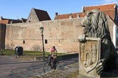 与女性骑自行车的人和城市墙壁,埃尔堡的街道视图 免版税库存照片