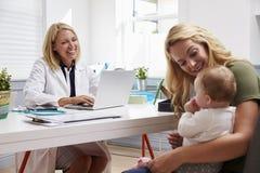 与女性医生In Office的母亲和婴孩会谈 免版税库存照片