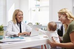 与女性医生In Office的母亲和婴孩会谈 免版税图库摄影
