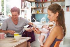 与女婴用途数字式设备的家庭在早餐桌上 免版税库存照片