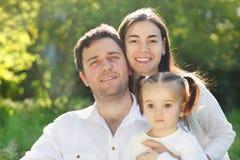 与女婴的愉快的年轻家庭 免版税库存图片