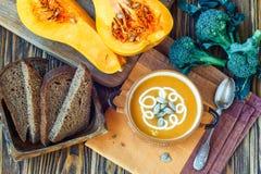 与奶油、新鲜的南瓜和南瓜籽的烤南瓜汤在木背景的板材 复制空间 库存照片